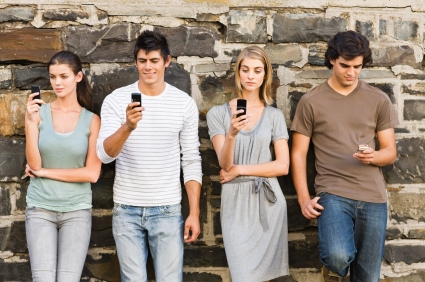 Full length of young men and women holding cellphone